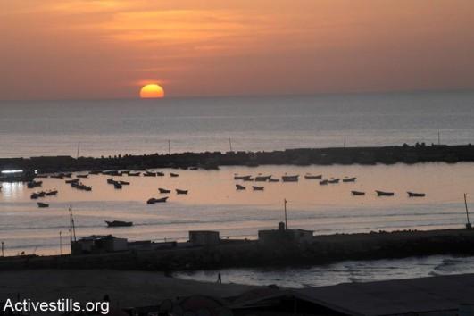 The sun setting on the Mediterranean Sea where fishing boats are docked at Gaza City Port, Gaza City, Gaza, February 5, 2012 (photo: Activestills)