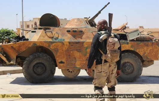 A fighter from the Islamic State stands in front of an armored personnel carrier. (photo: Islamic State)