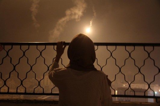 """Lara Aburamadan, a 22-year-old freelance photographer, has lived through three full-scale assaults on Gaza. She'd never seen the Israelis use this many flares, though. """"It was daytime at night,"""" she tells me. """"Very weird."""" (photo: Assad Saftawi)"""
