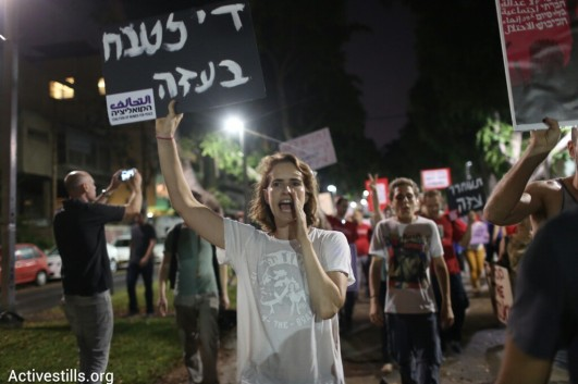 An Israeli protester holds a sign reading 'End the massacre in Gaza,' at a demonstration against Israel's assault on the Strip, Tel Aviv, August 23, 2014. (Photo: Activestills)