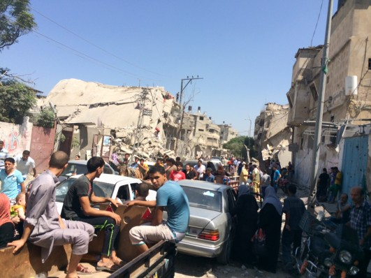 Residents of Shejaiya rush to retrieve their belongings during a temporary ceasefire, August 1, 2014. The ceasefire fell apart soon after and fighting in the area resumed (photo: Samer Badawi)