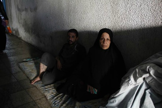 52-year-old Sabah Qtati (r) fled fighting in Gaza's Zeitoun neighborhood 17 days ago. She now lives in a hallway of Shifa hospital, next to the morgue. (photo: Samer Badawi)