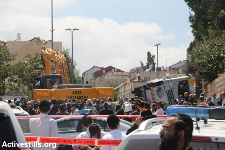 Police cordon off area after a Palestinian man rams digger into a public bus in Jerusalem. (photo: Activestills.org)