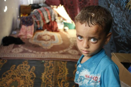 Three-year-old Firas Farhat lives with his brother, father and mother in a makeshift tent on a sidewalk outside Shifa Hospital. Their home in Gaza's Shejaiya neighborhood was destroyed by Israeli shelling. (photo: Samer Badawi)