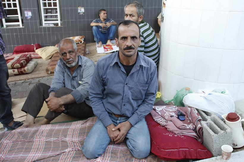 46-year-old Rafeeq Ibrahim hasn't returned to his home since fleeing Israeli shelling on July 17. He, his wife, and four daughters live on blankets outside the Shifa Hospital emergency room. (photo: Samer Badawi)
