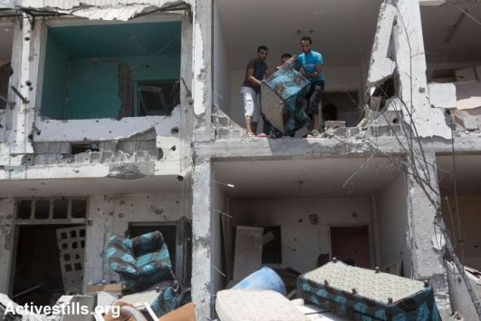 Palestinians salvage furniture from the ruins of Al-Nada towers after they were destroyed by Israeli strikes in Beit Hanoun, northern Gaza Strip, August 4, 2014. The towers had 90 flats. So far, Israeli attacks have killed at least 1,870 Palestinians, and injured 9,470 since the beginning of the Israeli offensive (photo: Activestills)