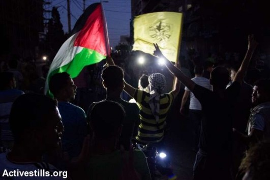 Palestinians flash victory signs as hundreds of Gazans gather in the streets to celebrate the ceasefire between Israel and Hamas on August 26, 2014 in Gaza City. (photo: Activestills)