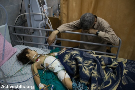 A Palestinian man watches on as a child breathes through a medical ventilator. (photo: Activestills.org)