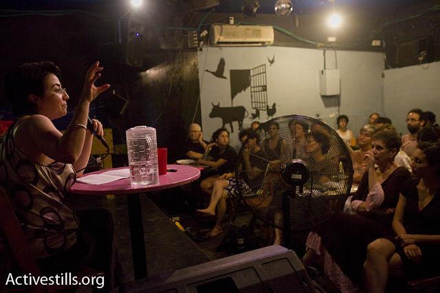 MK Haneen Zoabi speaks to a crowd at the Rogatka bar in Tel Aviv. (photo: Activestills.org)