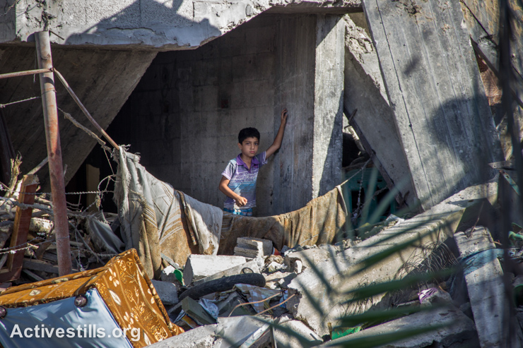 A Palestinian child stands in a destroyed house in the Shujayea neighborhood, which was heavily attacked during the latest Israeli offensive, east of Gaza City, September 4, 2014. During the seven-week Israeli military offensive, 2,101 Palestinians were killed, including 495 children, and an estimated 18,000 housing units have been either destroyed or severely damaged, leaving more than 108,000 people homeless. (Activestills.org)