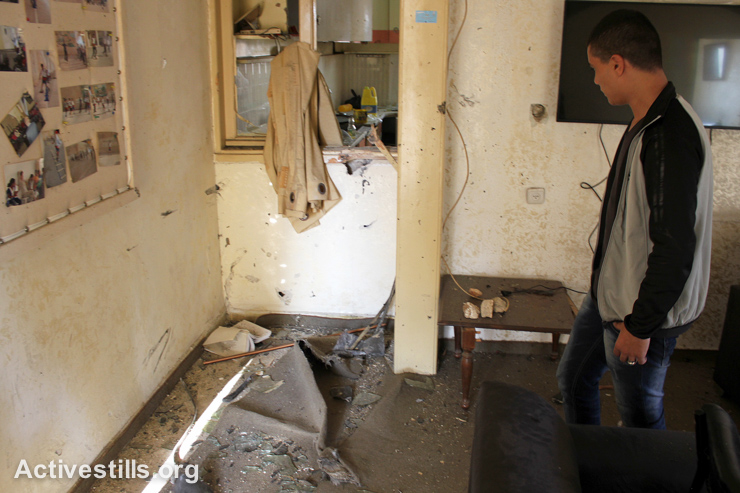 A Palestinian examines damage to a youth sport club which was raided by Israeli forces in the West Bank city of Nablus, September 3, 2014. Israeli forces arrested 26-year-old Husam Al-Din Abu Riyala, who was injured by live bullets, while others managed to escape. (Activestills.org)