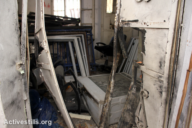 Steel doors lie blasted open after Israeli forces raided a multi-story building that included a youth sports club and center for children with disabilities in the West Bank city of Nablus, September 3, 2014. (Activestills.org)