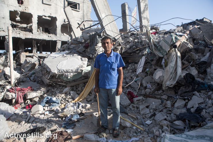 Maher, a resident of Shujaiyeh neighborhood, stands in front of his destroyed house in an area which was heavily attacked during the latest Israeli offensive, east of Gaza city, September 4, 2014. Maher lived in his house for 30 years before it was destroyed. Fifteen other members of his family were living in the building. He currently rents a flat while waiting for his home to be rebuilt. (Activestills.org)