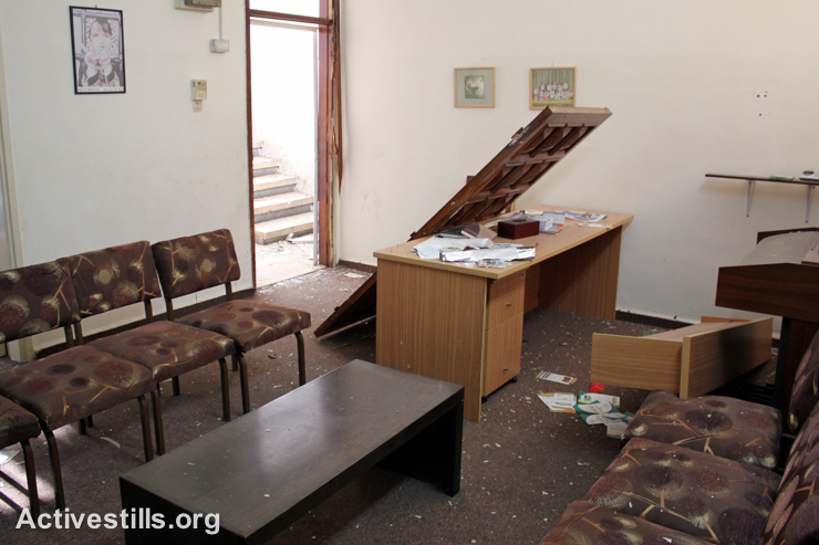 A door knocked off of its hinges lies among other damage caused to a center for children with disabilities in a building that was raided by Israeli forces in the West Bank city of Nablus, September 3, 2014. (Activestills.org)