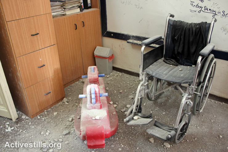 Toys and a wheelchair lie covered in dust and rubble after a center for children with disabilities was raided by Israeli forces in the West Bank city of Nablus, September 3, 2014. (Activestills.org)
