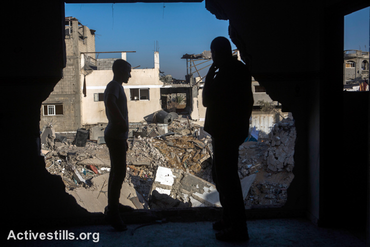 Palestinians look out from a damaged house in Shujaiyeh neighborhood, September 4, 2014. (Activestills.org)