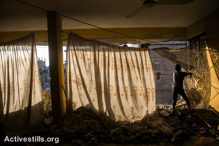 A Palestinian child looks outside from a damaged house in Shujaiyeh neighborhood, which was heavily attacked during the latest Israeli offensive, Gaza City, September 4, 2014. The family hung curtains where walls were blown out. (Activestills.org)