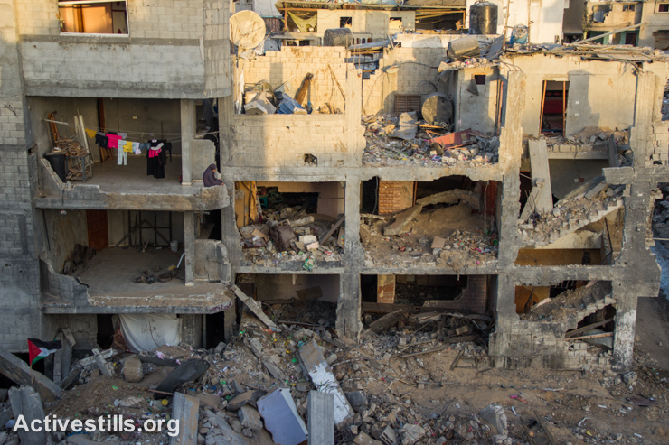 A Palestinian woman sits near laundry hanging over a destroyed quarter of the Shujaiyeh neighborhood, Gaza City, September 4, 2014. (Activestills.org)