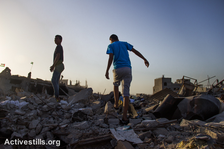 Youth walk among the rubble in a destroyed quarter of the Shujaiyeh neighborhood, which was heavily attacked during the latest Israeli offensive, east of Gaza City, September 4, 2014. (Activestills.org)