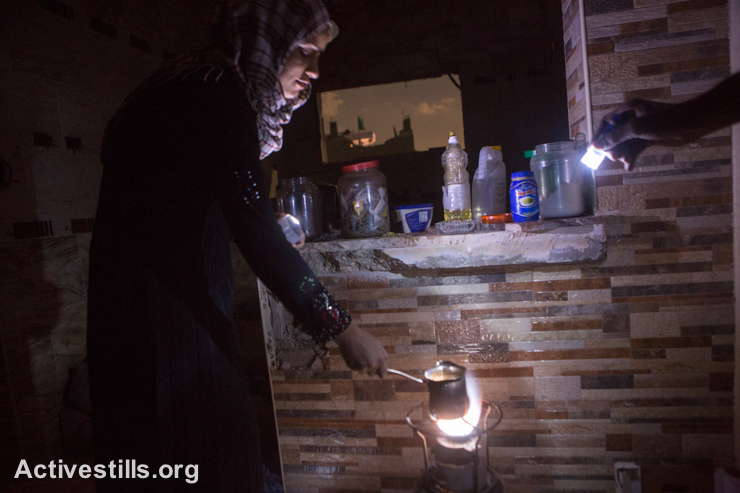 A member of the Atesh family prepares coffee illuminated by a flashlight in her partially destroyed home in the Shujaiyeh neighborhood, Gaza City, September 5, 2014. The family came back after the announcement of the truce. They have no electricity or water. (Activestills.org)
