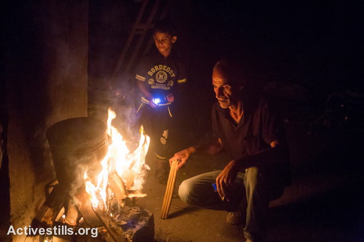 Hamde Atesh sits near a fire in his half-destroyed home in Shujaiyeh neighborhood, Gaza City, September 5, 2014. His family fled their home on July 12 after the Israeli military called to warn them to evacuate before they bombed the building next door. (Activestills.org)