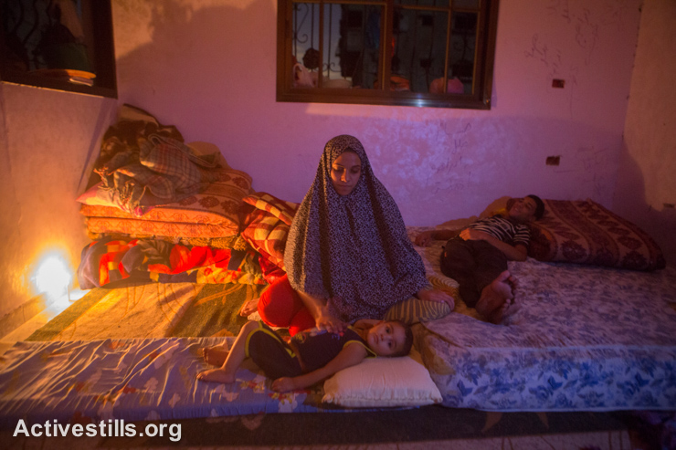 Members of the Atesh family sit in a room lit by a candle in their partially destroyed home in Shujaiyeh neighborhood, Gaza City, September 5, 2014. Due to the Israeli attacks, the electricity infrastructure has been damaged and most homes have no electricity or water. (Activestills.org)
