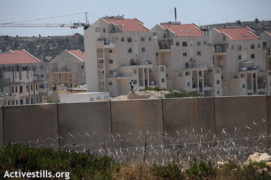 """Israel's separation barrier stands on land belonging to the Palestinian village of Bil'in; the wall was built surrounding the Israeli settlement of Modi'in Illit (seen in the background). In a protracted court battle, Bil'in managed to win back some of its land but landowners are still cut off from a significant portion which has been appropriated by the Jewish settlement – both to build on and as a """"security zone."""" (Anne Paq/Activestills.org)"""