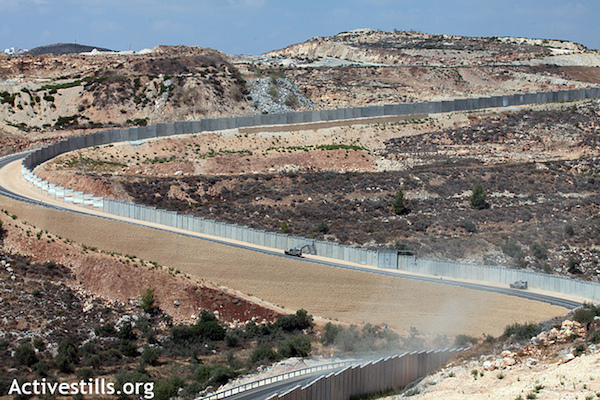 The Israeli separation barrier snakes through the West Bank. (Photo by Anne Paq/Activestills.org)
