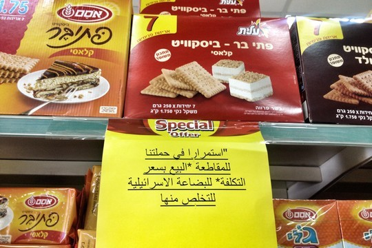 """A sign near the entrance of a grocery store in Ramallah: """"As part of our participation in the boycott campaign of Israeli goods we are selling these products at cost in order to get them off of our shelves."""" (Photo by Jessica Devaney/Just Vision)"""