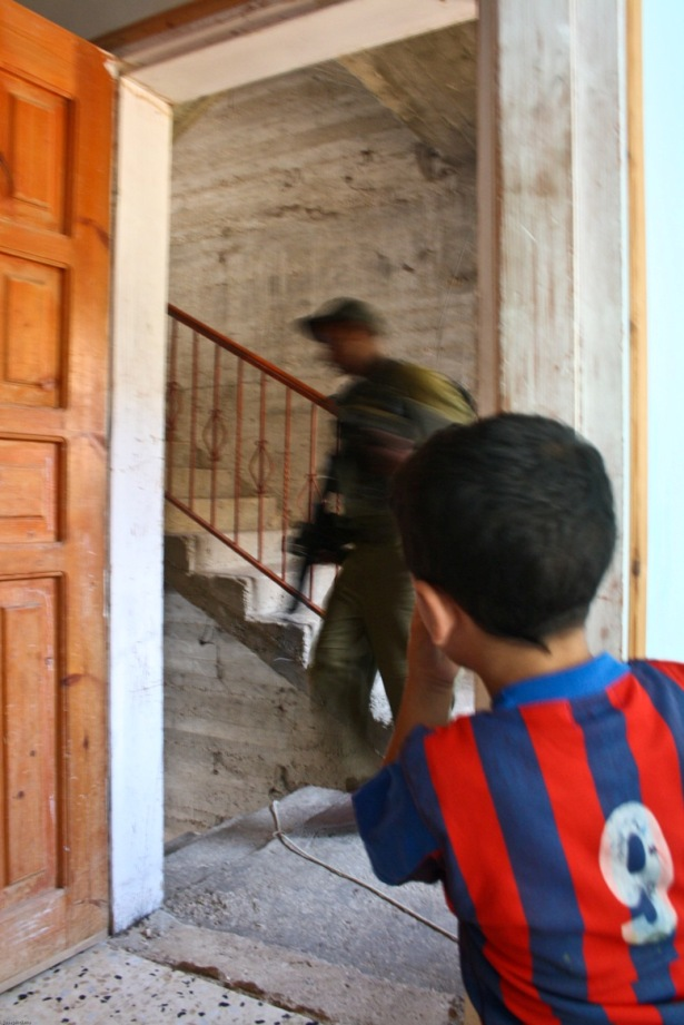 Israeli soldiers march through the Salima family home. Photo by Joseph Dana.