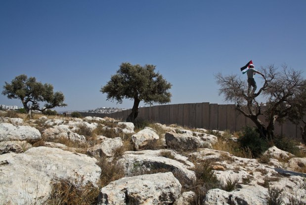 A Palestinian protester is seen in front of the Separation Wall in Ni'ilin. Photo by Joseph Dana