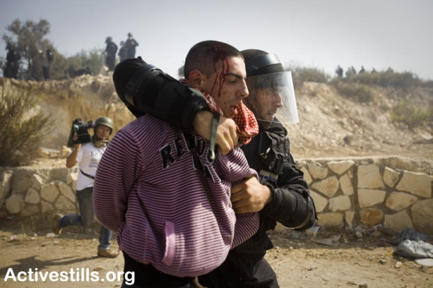 Israeli policeman officer detain a protester during clashes in Umm el-Fahm October 27, 2010.