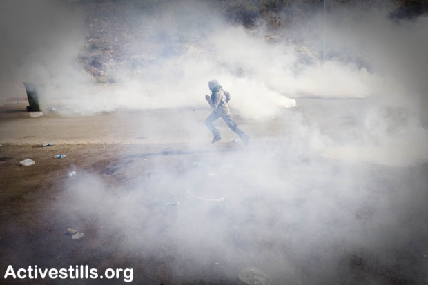 A demonstrator runs inside a cloud of tear gas during clashes in Umm el-Fahm October 27, 2010.