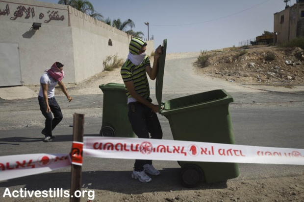 A demonstrator hides behind a garbage cans during clashes in Umm el-Fahm October 27, 2010.  (photo: Oren Ziv)