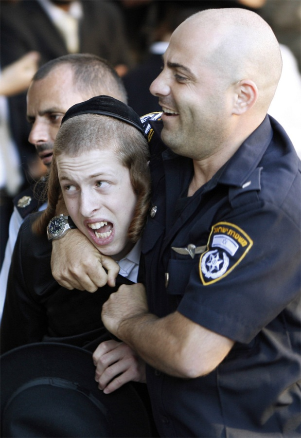 Policeman arresting a Hassidic kid (image: tsofar.co.il)