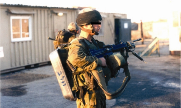 """A soldier prepared for a """"presence"""" patrol in a Palestinian village with a Casserole, used to create noise in the village. 2004, Bateer (photo: Breaking the Silence)"""
