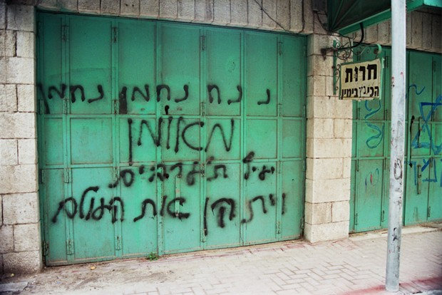 "Graffiti on a Palestinian shop: ""Rabbi Nachman will kick out the Arabs"" (photo: Breaking the Silence)"