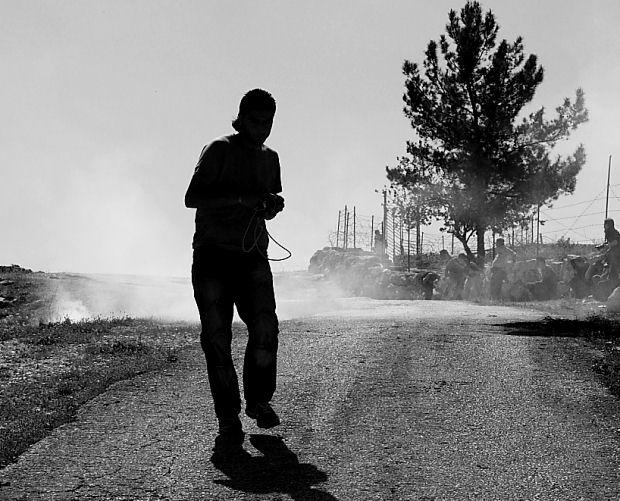 A Palestinian demonstrator tries to avoid the tear gas, Bil'in, 2009 (Yossi Gurvitz)