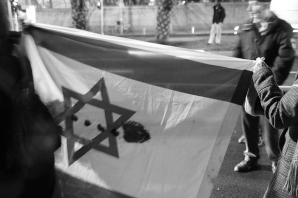 Demonstrators holding up a blood-stained Israeli flag (photo: Lisa Goldman)