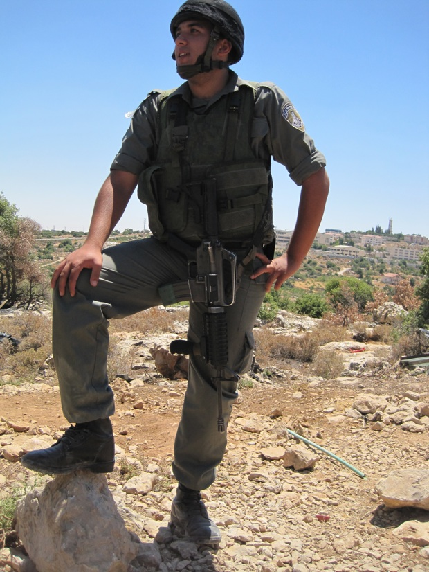 Soldier standing atop a protected outpost by Kiryat Arba. (Photo: Mairav Zonszein)