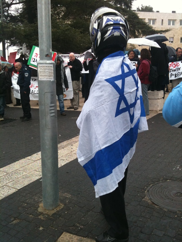 An indignant onlooker wrapped in an Israeli flag