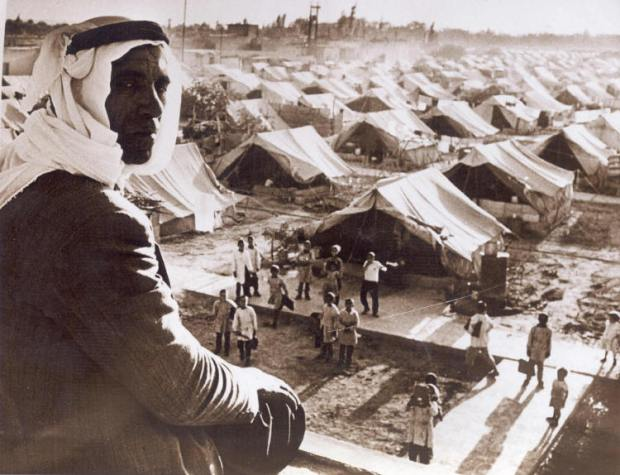 A Palestinian man watches a school in a refugee camp, 1948 (photo via wikimedia. license CC)