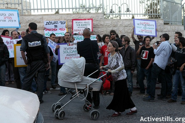 Settler passes by demonstrators against Maaleh Zeitim settlement in ras el-Amud (photo: Activestills.org)
