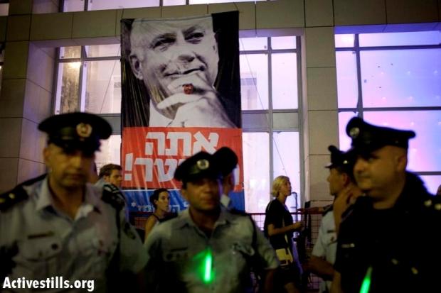 "Policemen. Sign reads ""Netanyahu, You are fired!"" (photo: Oren Ziv/Activestills)"
