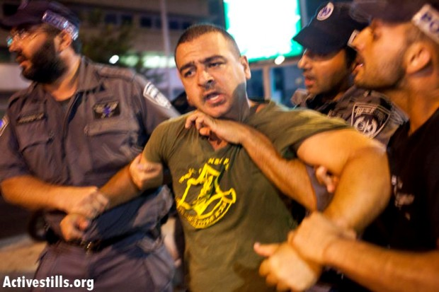Protester wearing an unofficial IDF T-shirt detained by police after march for social justice (photo: Oren Ziv/activestills)