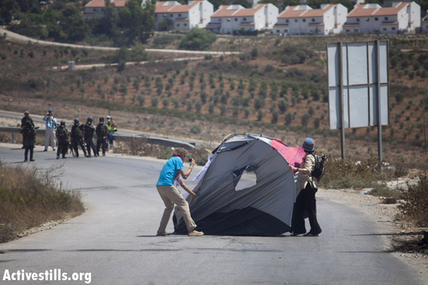 Protesters in the West Bank village of Nabi Saleh attempt to erect a tent on Friday 12 August 2011. Photo by Oren Ziv/activestills.org