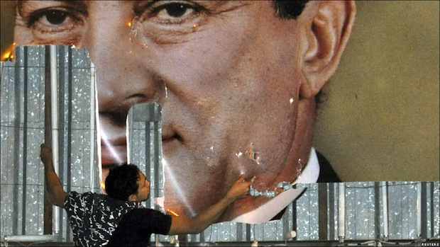 An Egyptian protestor defaces a picture of former president Hosni Mubarak in Alexandria (photo: flickr / antonello_mangano)