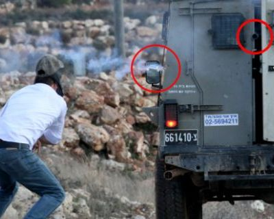Mustafa Tamimi, a second before he was shot. The weapon and tear gas canister are circled in red (Photo: Haim Scwarczenberg)
