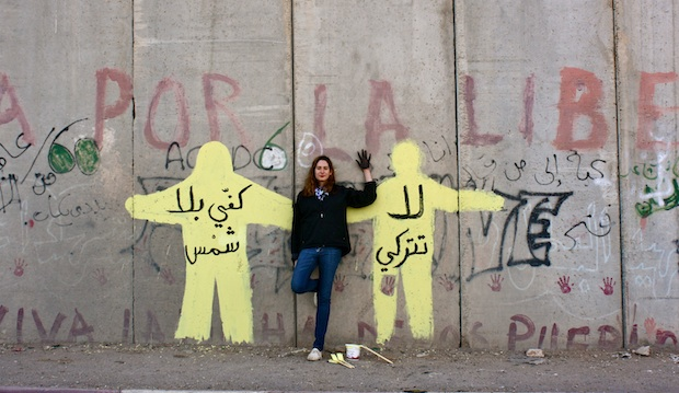 """The author against a mural she painted on the separation wall. """"Do not take the sun out of my palm,"""" it reads."""