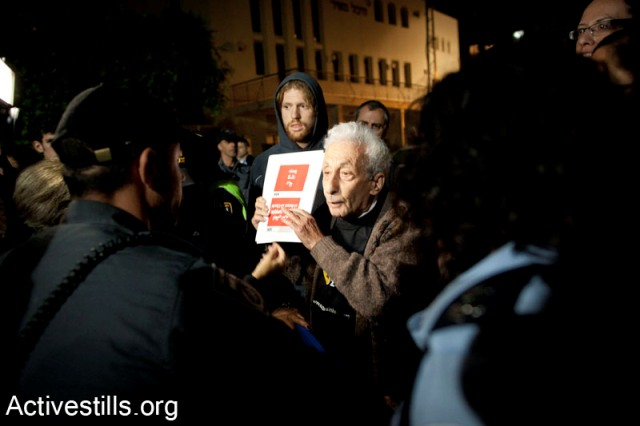 Zochrot activist holding a sign with the name of a Palestinian village (Activestills)